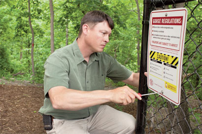 Todd Bittner installs a warning sign