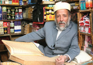 A shopkeeper reading the Koran in Yemen
