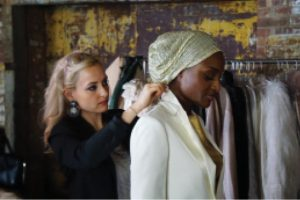 Begler on the left adjusts a model's beige embroidered headscarf.