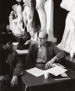 A.R. Ammons sits at a cafe table with a student in the Temple of Zeuss.