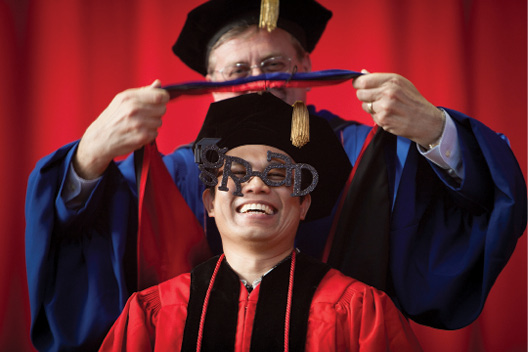 "A PhD student receives his hood; he wears ""Grad"" glasses."