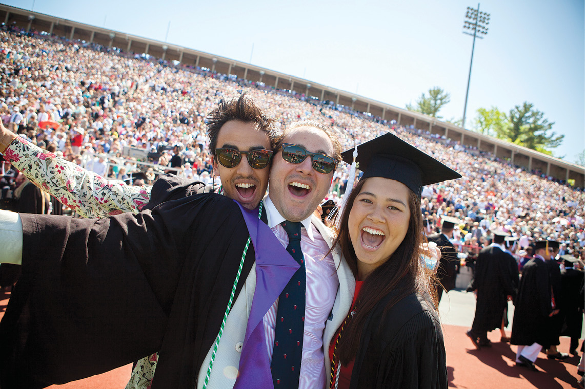 Three grads pose for a selfie with the Crescent in the background.
