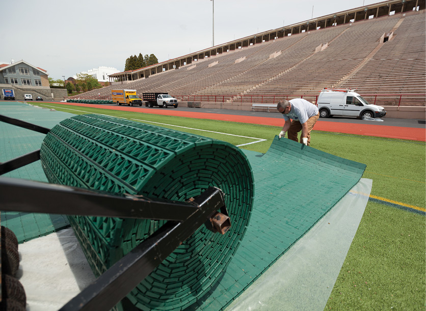 A worker unrolls protective matting on top of the football field astroturf.