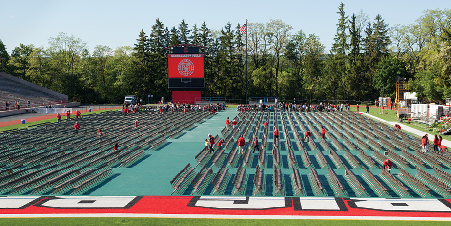 Volunteers ready chairs on the field at Schoellkopf.