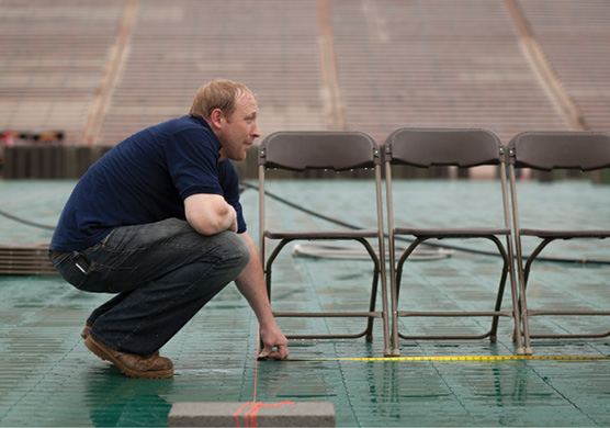 A worker measures space for chairs on the football field