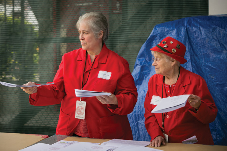 Two red-coated volunteers hand out programs.