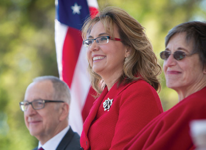 Gabby Giffords smiles the podium, next to David Skorton.