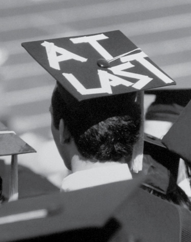 "The back of a student's head, who's wearing a mortarboard that says ""AT LAST"" in masking tape"