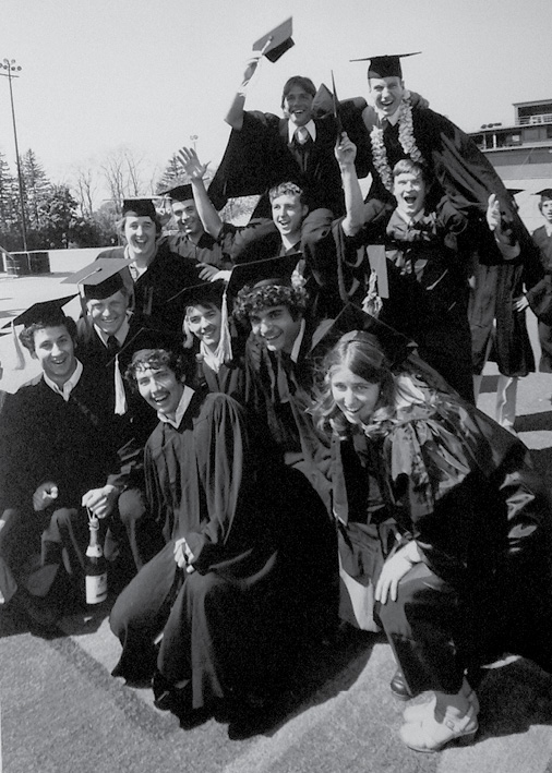 A group of happy students from the class of 1990 post for cameras.