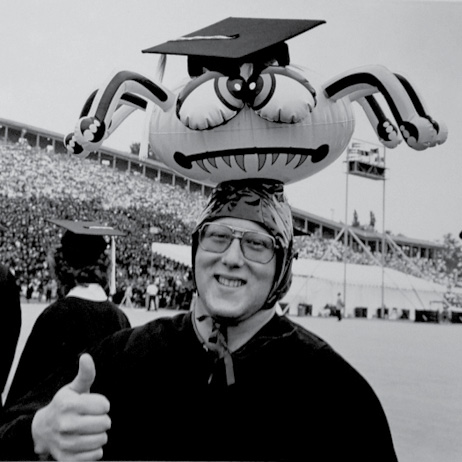 A student wears an inflatable goofy spider on his head, which in turn wears the student's mortarboard.