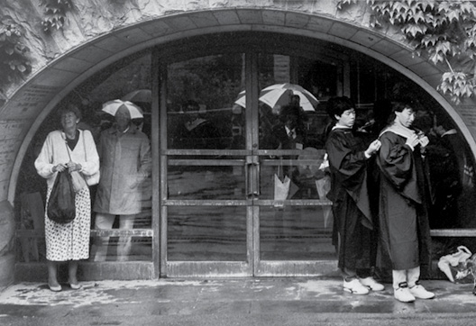 Visitors and grads huddle in the shelter of the Uris Library entrance.