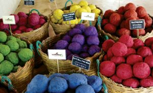 Baskets of paper pulp, colored green, purple, yellow blue and three shades of red.