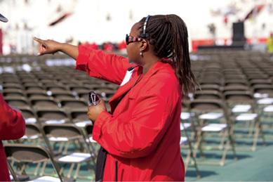 A red-jacketed usher helps on the field before grads arrive.
