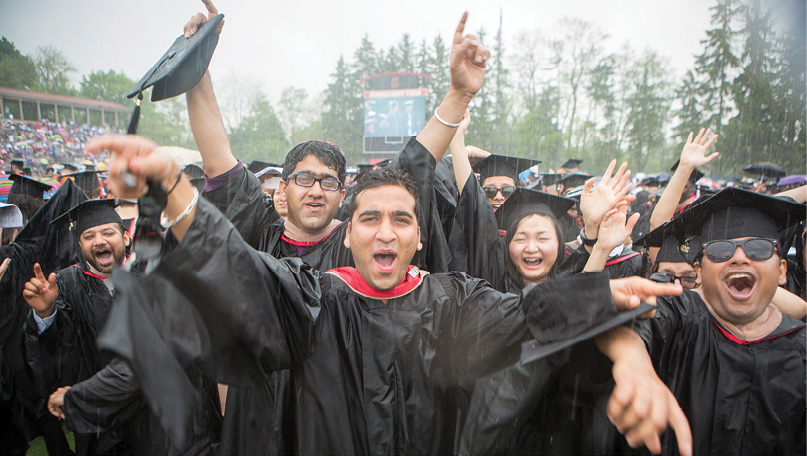 Soaking wet grads celebrate during a downpour.