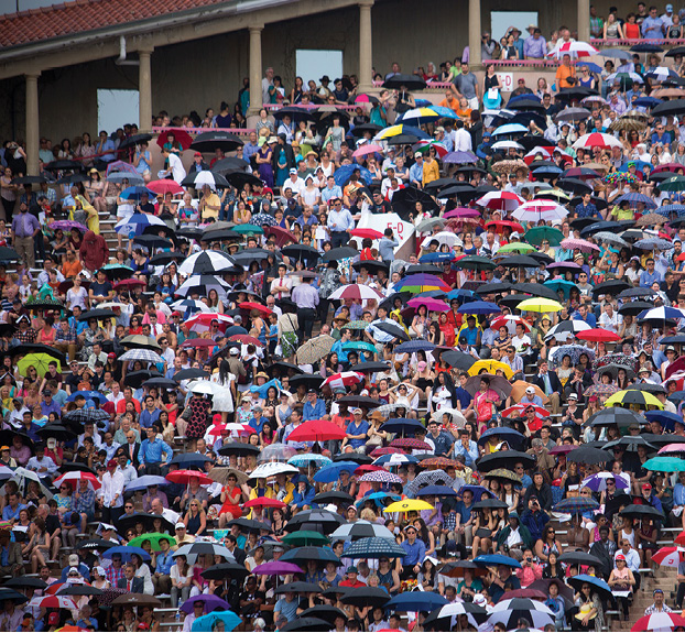 A rainbow of umbrellas shield graduation attendees during a rainstorm at Schoelkopff.