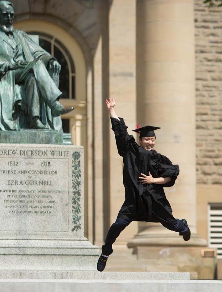 A new graduate jumps for joy in front of the AD White statue.
