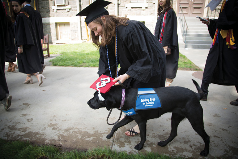 A grad adjusts her guiding eyes dog-in-training's red CU mortarboard.