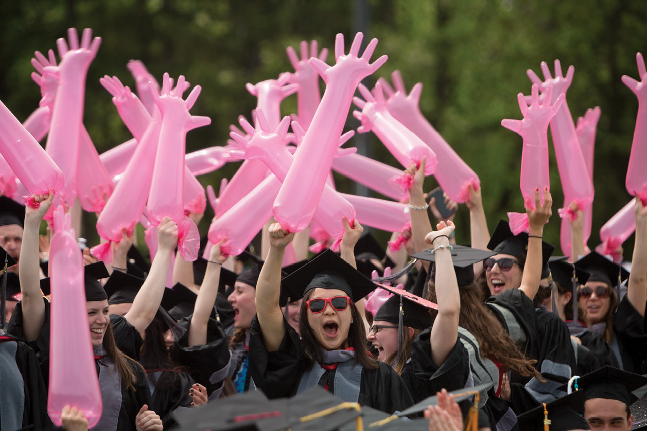 Graduating veterinarians wave pink inflated exam gloves