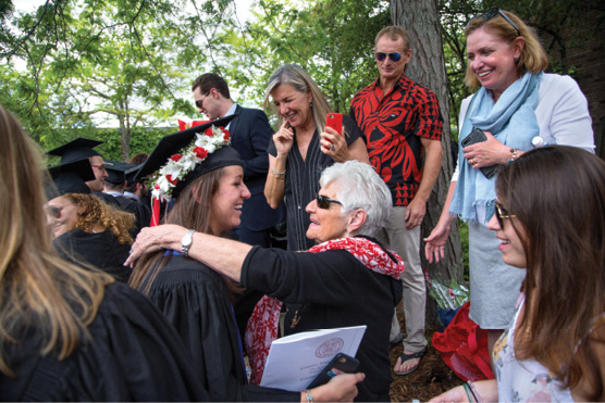 A grad hugs her grandmother, surrounded by happy family.