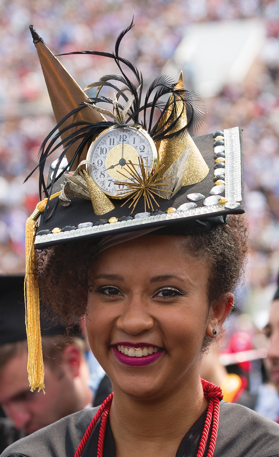 A smiling grad displays a mortarboard decorated with a clock and additional bling.