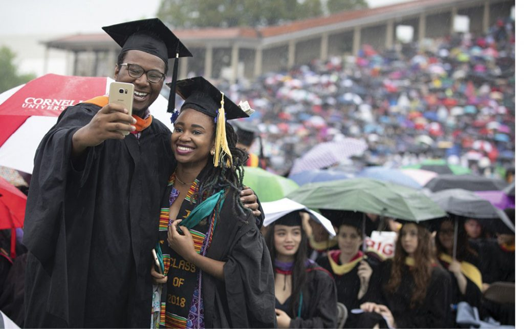 Two graduates take selfies at graduation.