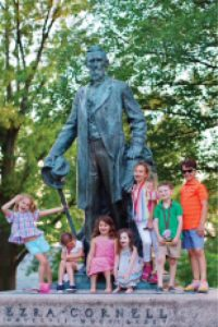 A group of kids pose in front of Ezra statue