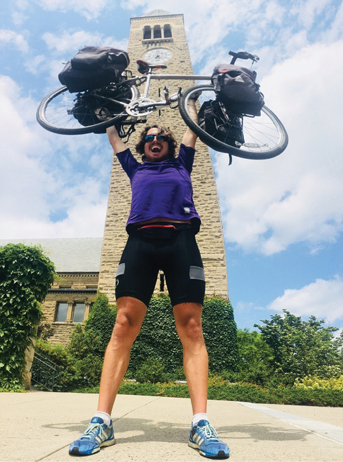 Epstein holds his touring bike triumphantly over his head in front of the clocktower