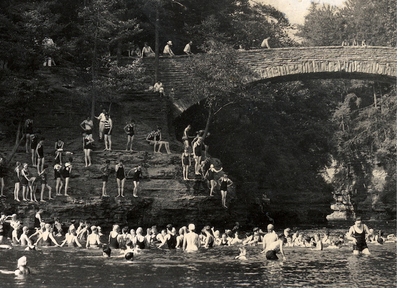 Archival photo of dozens of students swimming in Beebe; some jump off the bridge.