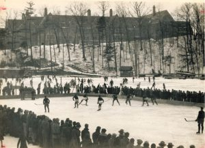 Archival photo of a hockey game played on Beebe Lake, with spectators ringing the players