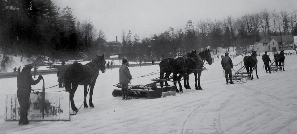 Horse teams drag ice scrapers on the frozen lake
