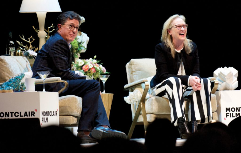 Colbert and Streep on a stage with flowers during an interview