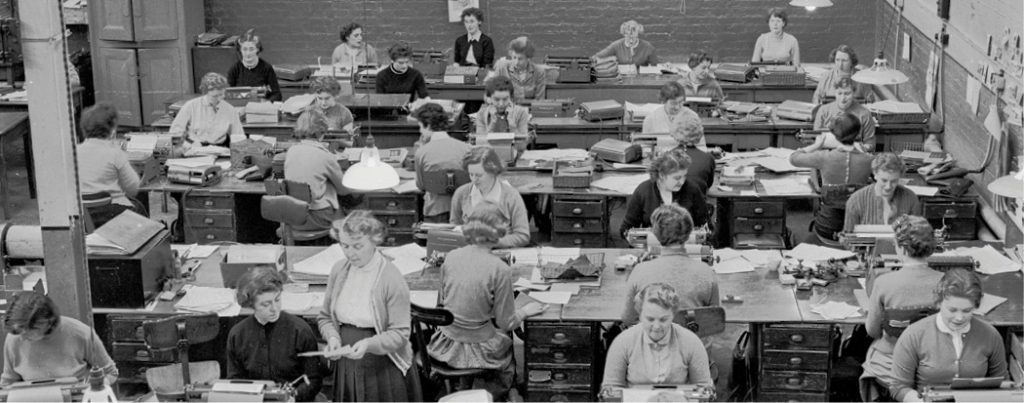 A picture from the 1960s of a room of women workers at rows of desks.