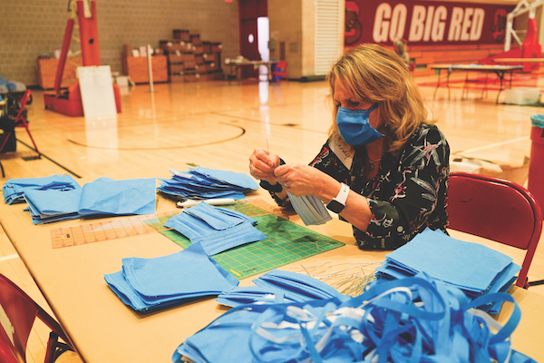 A woman wearing a face mask sews a pile of face masks at a table in the gym of Bartels hall.