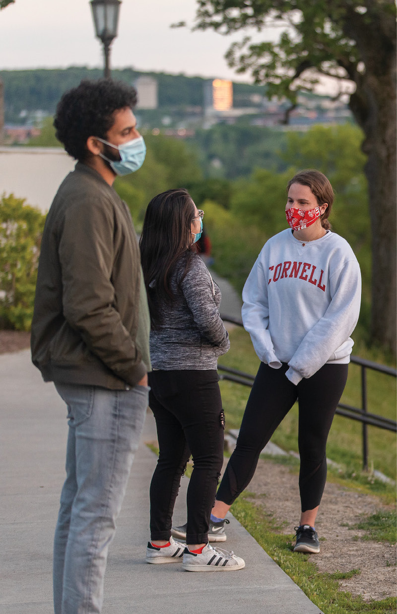 Three students wearing masks hang out at the top of the slope in the early evening hours.