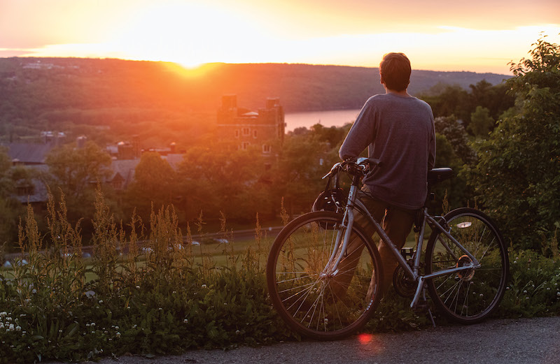 A bicyclist leans against his ride as the sun sets over the opposite side of the valley.