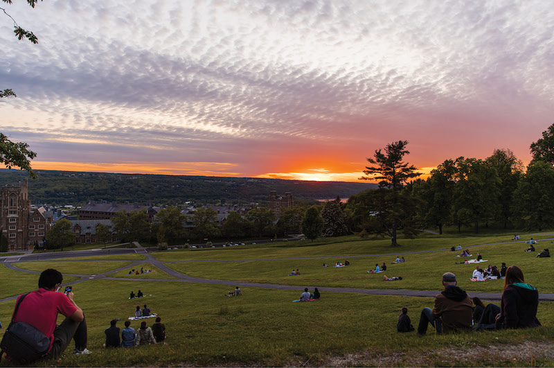 Taken from the top of Libe Slope, looking westward over the valley and lake, a handfull of students watch the sunset, scattered sparingly across the hill.